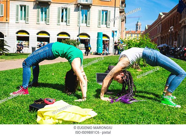 Women doing hand stand with arched back, Milan, Italy