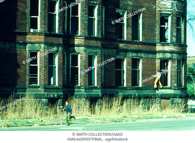 One boy runs while another scales the side of an abandoned building in Chicago, Illinois, 1973. Image courtesy National Archives