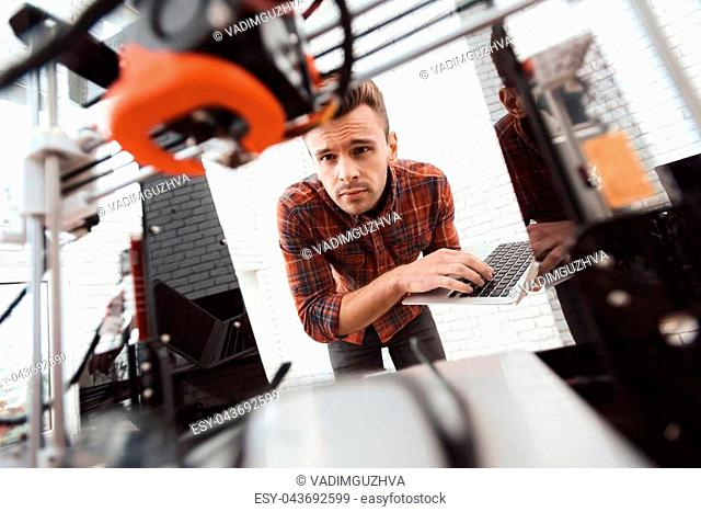 A man with a laptop in his hands controls the process of printing a 3d printer. 3d printer has printed model of an apple. The man controls the process