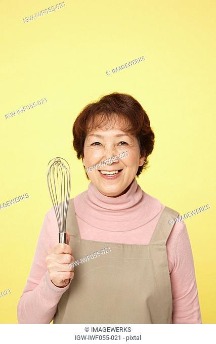 Senior woman holding egg beater, smiling