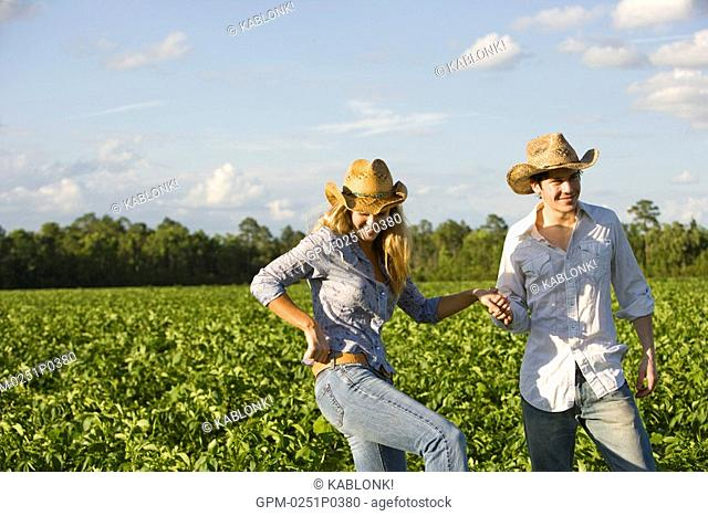 young couple standing in field wearing cowboy hat