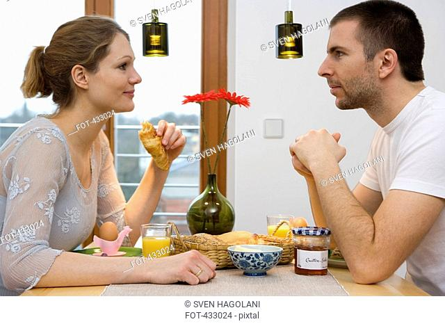 Young couple staring at each other over breakfast