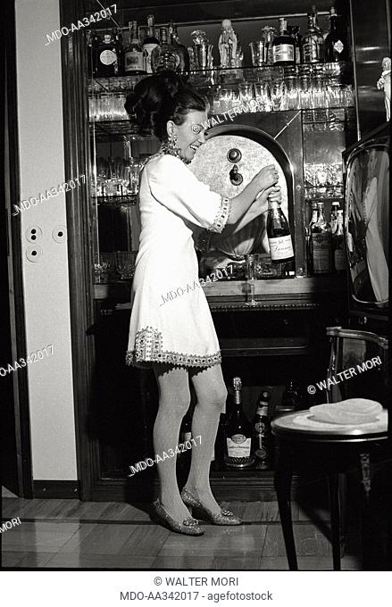 Portrait of Bedy Moratti in her house. The Italian actress Bedy Moratti opening a bottle at her home's bar corner. Milan, May 1968