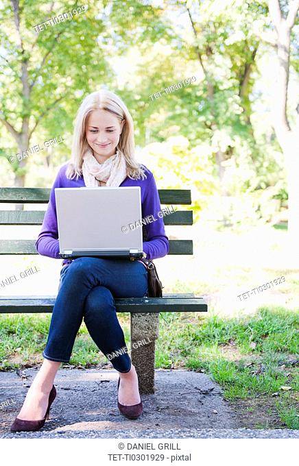 USA, New York, New York City, Manhattan, Central Park, Young woman sitting on bench and using laptop