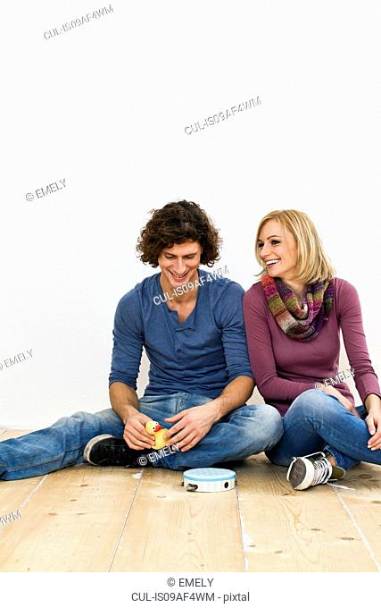 Studio shot of couple sitting on floor with toys