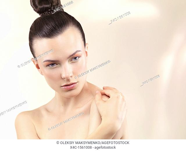 Beauty portrait of a young woman with wearing soft pastel color makeup and top knot hairstyle