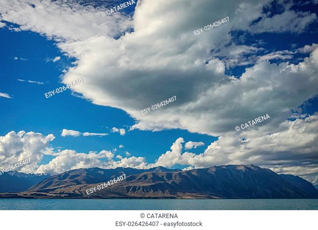 Beautiful background from The Lake Tekapo with mountains and deep blue cloudy sky. South Island, New Zealand