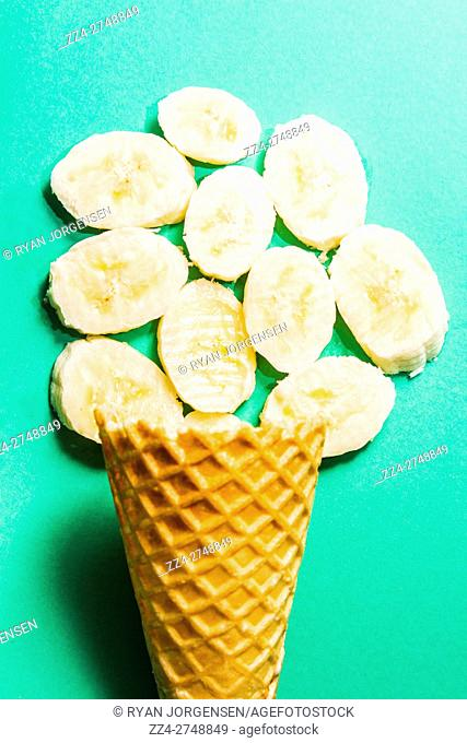 Desert concept of ice-cream cone with banana slices shaped as a scoop. Bananas artwork