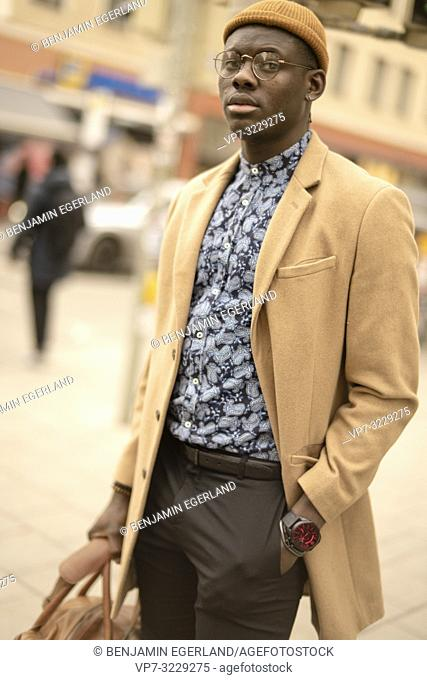 stylish man walking at street in city Munich, Germany. Streetstyle, male blogger fashion look