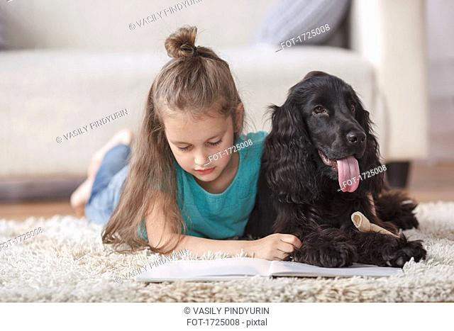 Cute girl reading book while lying by dog on rug at home