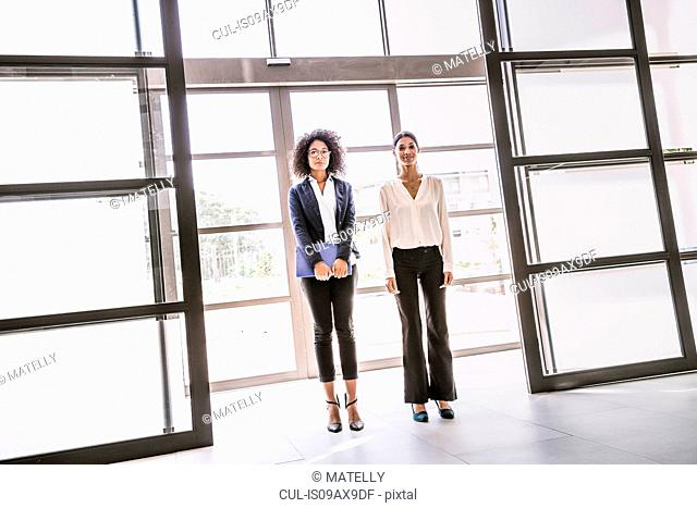 Portrait of two young businesswomen at office entrance