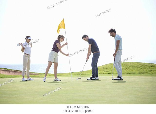 Friends putting on golf course