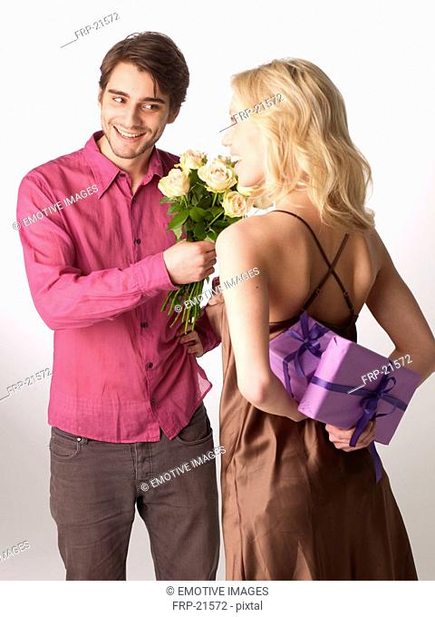 Woman with gift and man with bunch of flowers