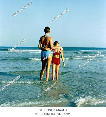 Girl and mother standing in sea