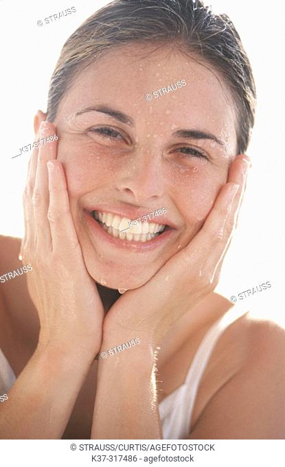 Young adult woman with clear skin splashing water on her face