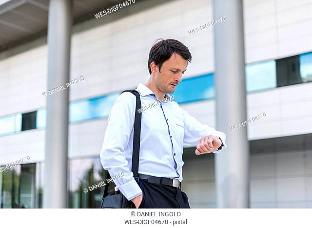 Businessman in the city checking the time
