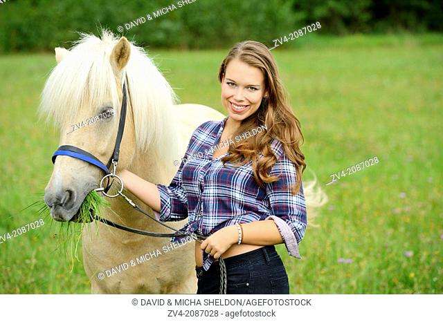Young woman with a Icelandic horse on a meadow, Germany
