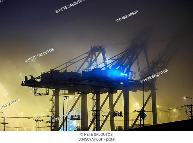 Misty view of harbor cranes at night, Seattle, Washington, USA