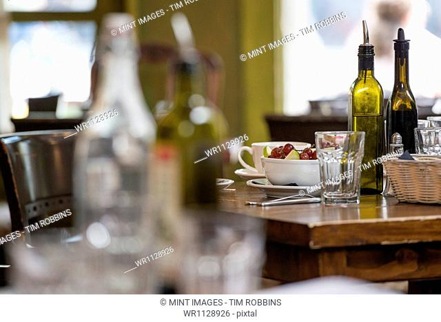 Interior of a city coffee shop or cafe. Tables laid for meals. Coffee cups and glasses. Bottles. Surface level