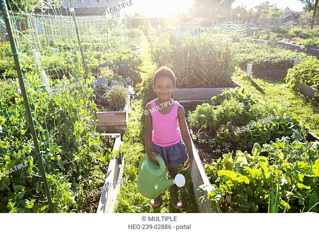 Portrait smiling girl with watering can vegetable garden