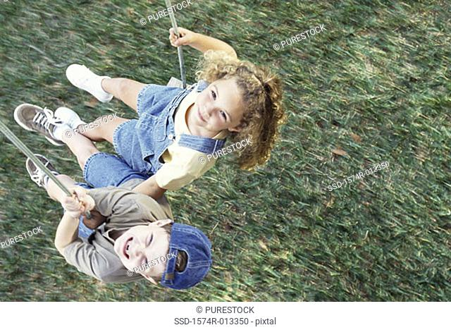 High angle view of a boy and girl swinging on a swing
