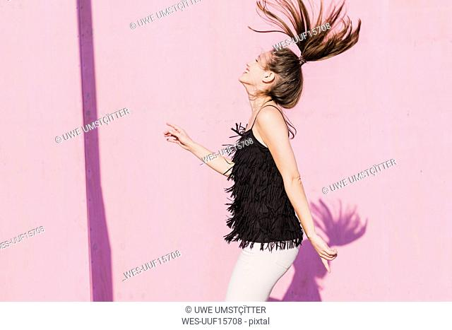 Happy young woman moving in front of pink wall