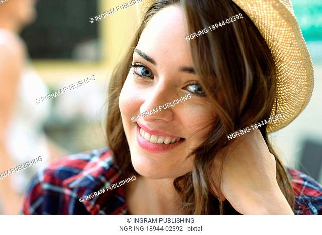 Close-up portrait of young woman with beautiful blue eyes wearing plaid shirt and sun hat