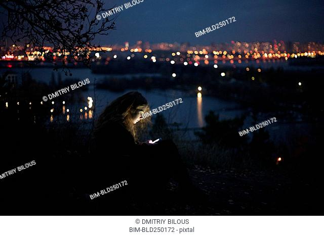 Caucasian woman standing near urban waterfront at night
