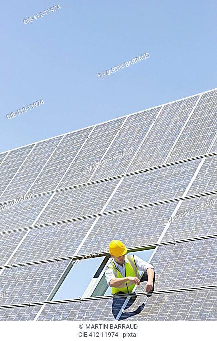 Worker examining solar panel in rural landscape
