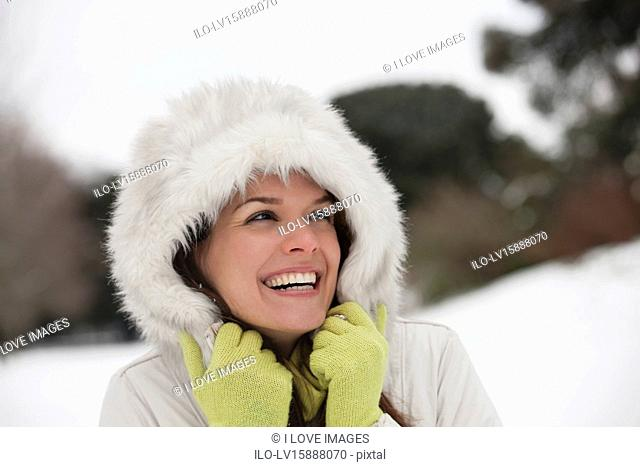 A young woman standing in the snow, trying to keep warm