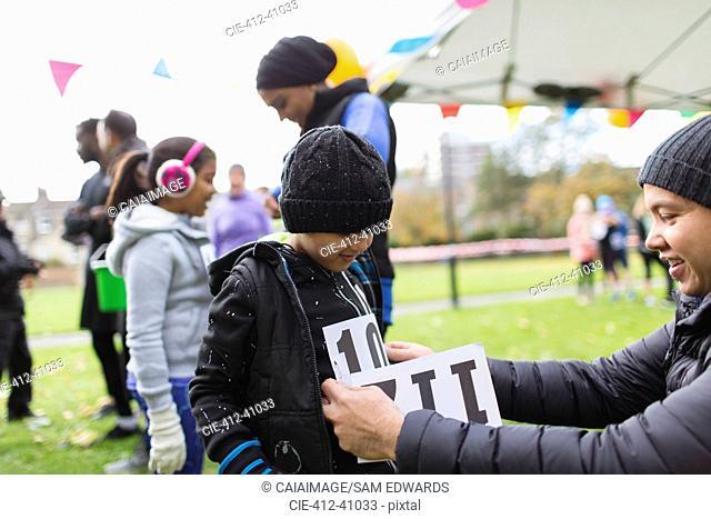 Father pinning marathon bib on son at charity run in park