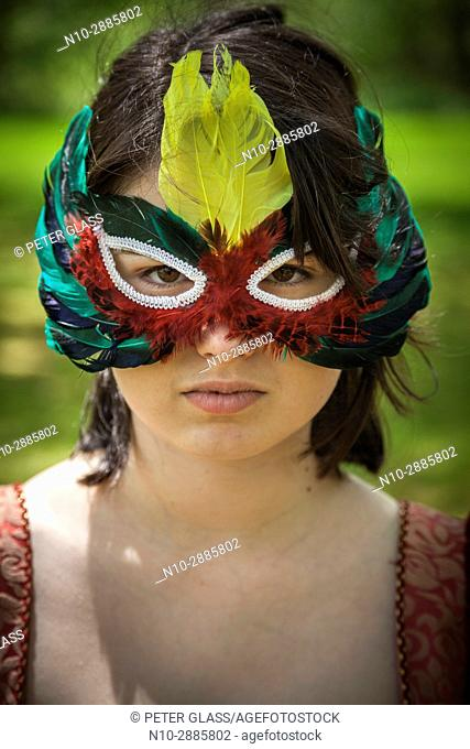Young woman, in a park, wearing a mask