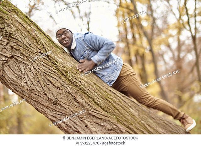 man chilling on tree, nature, in Englischer Garten in Munich, Germany