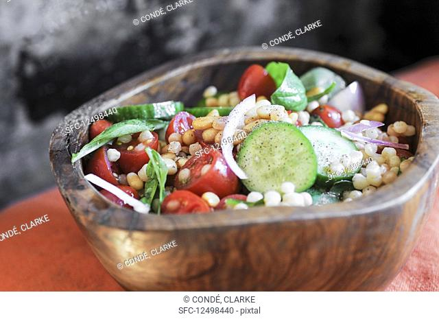 Israeli couscous salad with cucumbers, tomatoes and fresh basil in a wooden bowl
