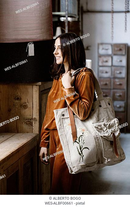 Smiling fashionable young woman with big shopping bag in a loft