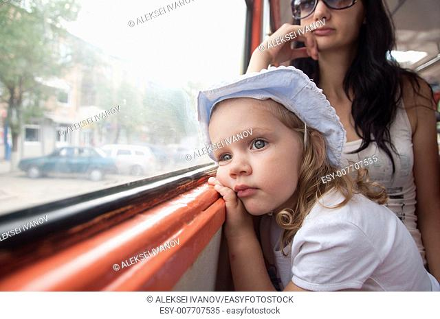 Little girl and mom goes to tram. Girl tired, thoughtfully, looking out the window