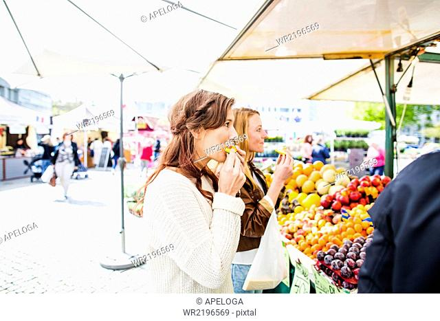 Women eating fruit while shopping at market