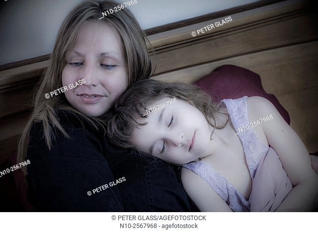 Mother and six year old daughter on her bed