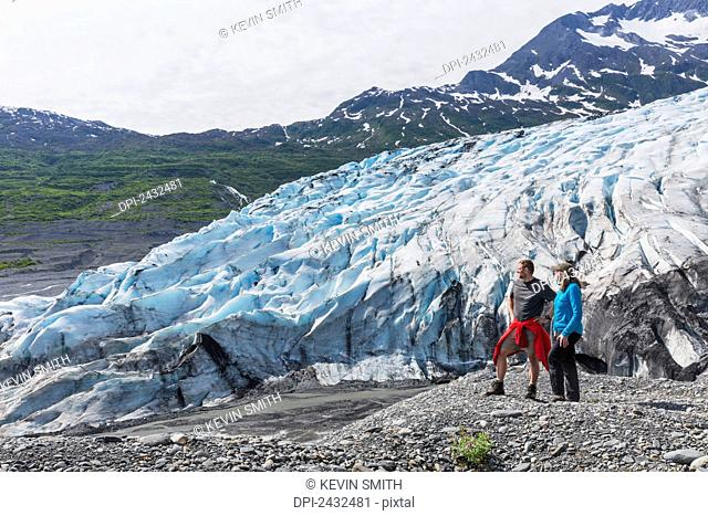 Couple standing on overlook in front of Shoup glacier, Shoup Bay State Marine Park, Prince William Sound; Valdez, Alaska, United States of America