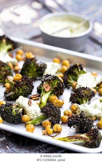 Aluminium tray with roasted broccoli florets and chickpeas, topped with garlic herb yoghurt, on an aged metal background
