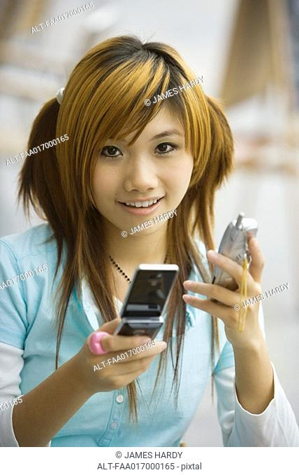 Young woman holding two cell phones, looking at camera