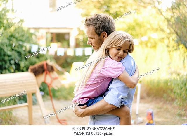 Father cuddling with daughter in garden