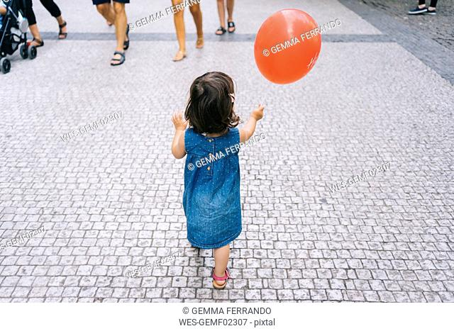 Back view of baby girl with red balloon walking on pavement