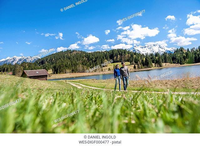 Germany, Bavaria, couple walking at lake Barmsee