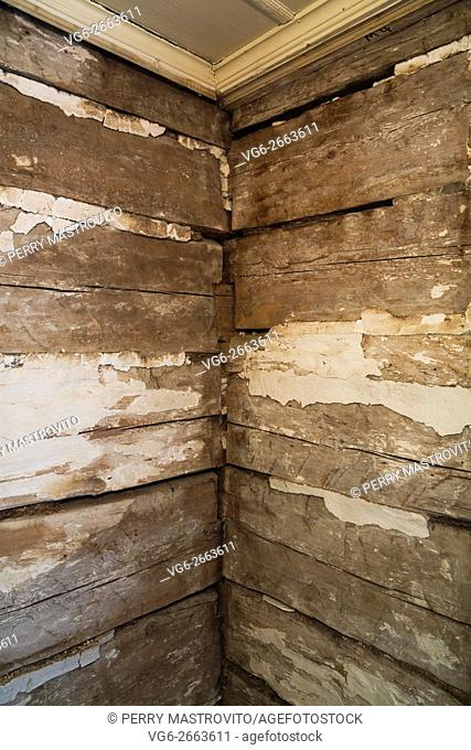 Stacked wooden beams and chunks of white plaster on walls in a room inside an old 1800s cottage style home, Quebec, Canada