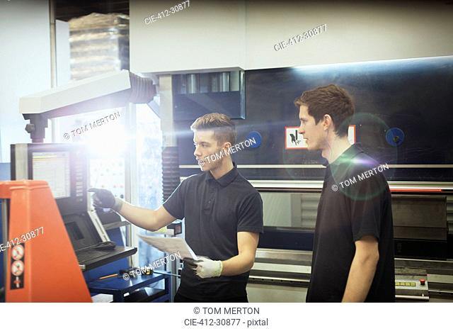 Worker training trainee at machinery control panel in steel factory