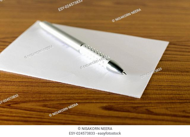 pen with white paper on wooden background