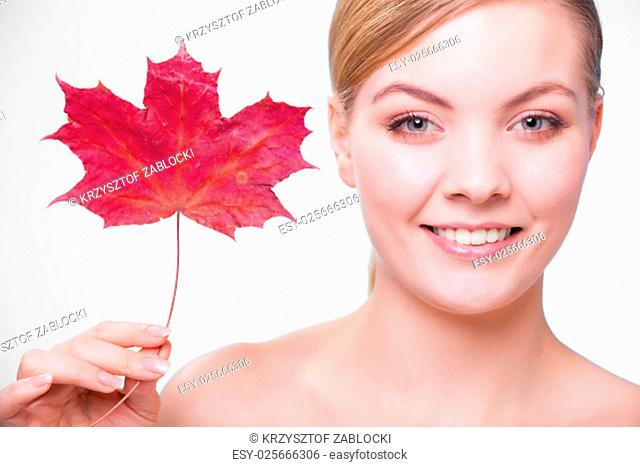 skincare habits. portrait of young woman with leaf as a symbol of capillary skin of red on gray. face of a girl taking care of her dry complexion