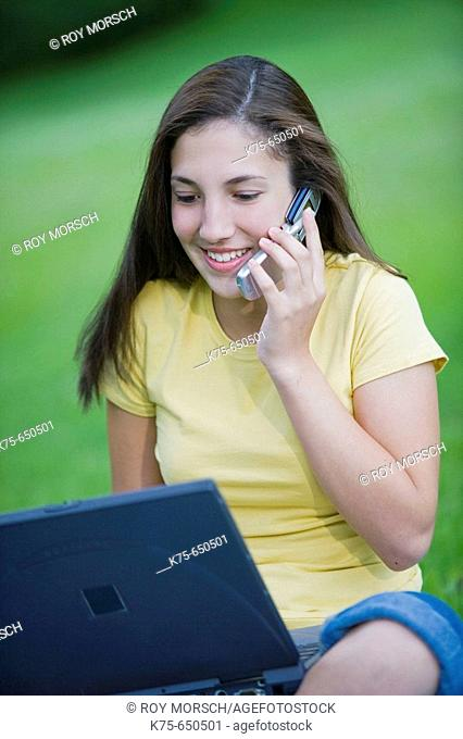 Teen using cell phone and laptop outdoors