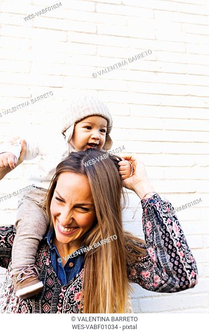 Happy mother holding her baby on shoulders